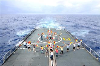 Photo: 在「手旗信號識別訓練」課程中,南沙營師生們特別排列成「海錨」隊形實施操演,感謝海軍官兵們一路上無微不至的照顧與安排。紅黃相間的手旗、海錨隊形、軍艦航行過的波紋與天海一線的景象,形成一幅優美的圖畫。(周力行軍聞社)