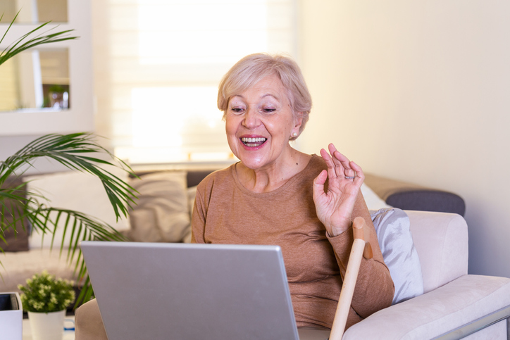 a senior woman talking to someone via video chat on her computer