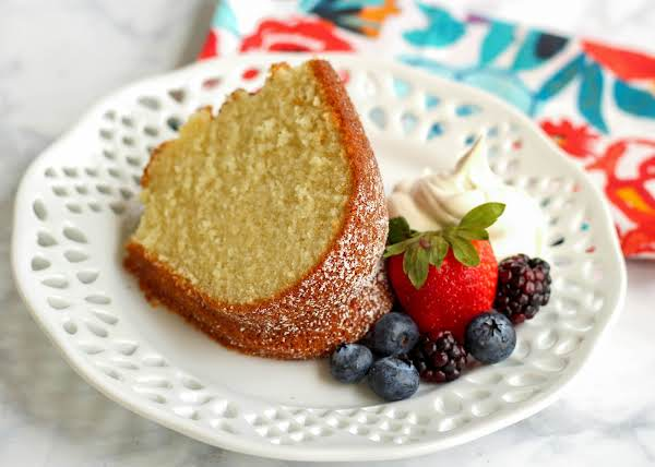 A Slice Of Pound Cake On A Plate With Berries.