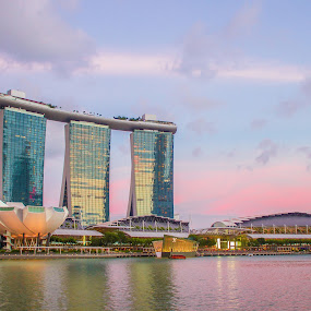 Marina Bay Sands At Sunset by Huy Yo - City,  Street & Park  Skylines ( illuminated, famous, reflection, skyline, metropolis, marina bay sands, travel, architecture, cityscape, singapore, marina bay, city, modern, sunsets, southeast, asia, sunshine, pink, commercial, central, downtown, water, clouds, structure, building, urban, cbd, tower, color, sunset, architectural, hotel, waterfront )