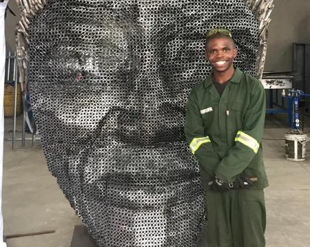 "Minenhle Nxele with his artwork ""Mandela's Face"" at the Global Scrap Metal workshop in Pietermaritzburg."