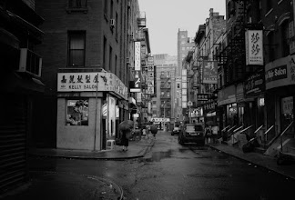 """Photo: """"The gleam in the eye of the clouds...""""  New York Photography: Chinatown  Under the weight of the sky's tears streets glisten reflecting the gleam in the eye of the clouds overhead. The day washes away slowly: its sorrows and joys melt into puddles under-foot.  It's on these sorts of evenings that all of the cares in the world pale in comparison to the momentary haze that engulfs the city: a sultry, sorrowful, sedate embrace.  --  You can view this post along with information about prints of this image if you wish at my site here:  http://nythroughthelens.com/post/15729539591/pell-street-chinatown-in-the-rain-new-york  -  Tags: #photography #writing #newyorkcity #manhattan #chinatown #rain #prose #poetry #blackandwhite #streetphotography #newyorkcityphotography #street"""