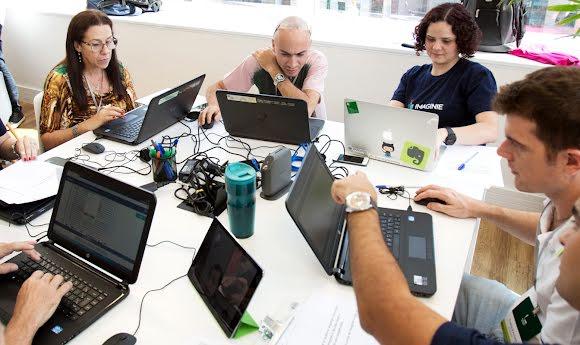 Voluntarios de Google se sientan alrededor de una mesa para preparar planes de lecciones digitales.