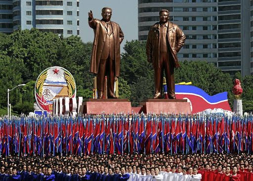 Anniversary parade: People carry flags in front of statues of North Korean founder Kim Il-sung, left, and late leader Kim Jong-il during a military parade marking the 70th anniversary of North Korea's foundation in Pyongyang on Sunday. Picture: REUTERS