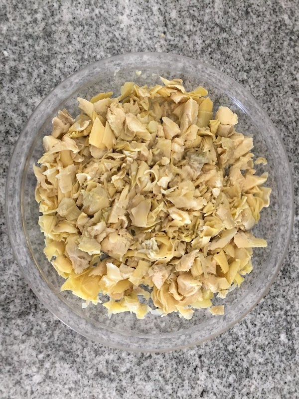 Drain water from artichokes and place in a bowl.  Chop the artichokes up...