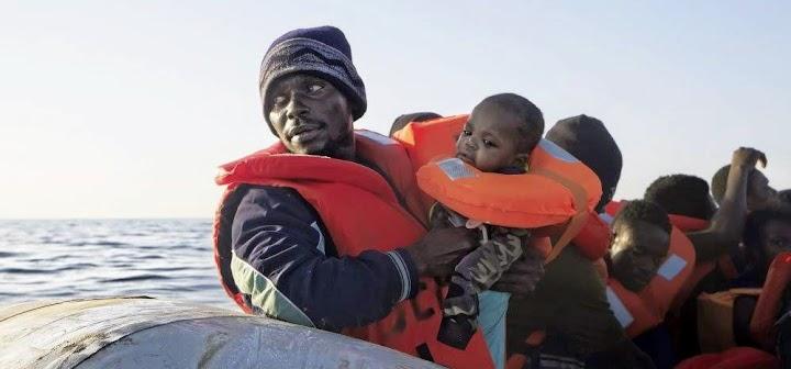 Flüchtling mit Kind im Schlauchboot.
