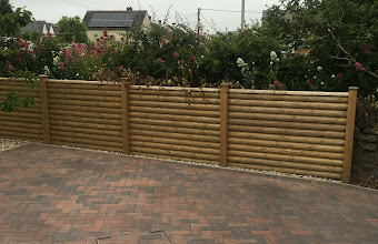 a brick driveway with a wooden garden fence