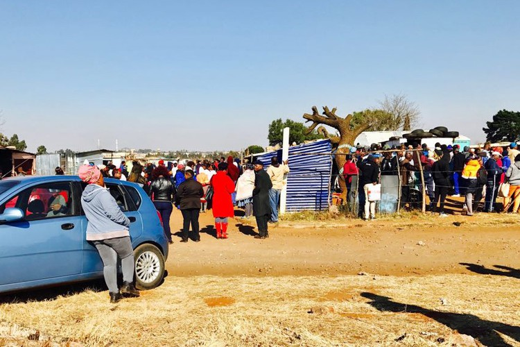 People queue with their ID documents to be registered by members of the EFF for a piece of land in Brakpan.