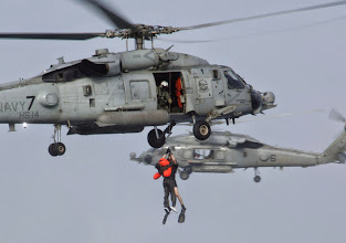 Photo: KADENA AIR BASE, Japan -- Tech. Sgt. Dawn Ryan is hoisted by a Navy HH-60G Pave Hawk helicopter from the aircraft carrier USS Kitty Hawk during water mass casualty training. The exercise provides a unique opportunity for Airmen and Sailors to work together in a maritime environment. Sergeant Ryan is assigned to the 18th Aeromedical Evacuation Squadron here. (U.S. Air Force photo by Master Sgt. Val Gempis)