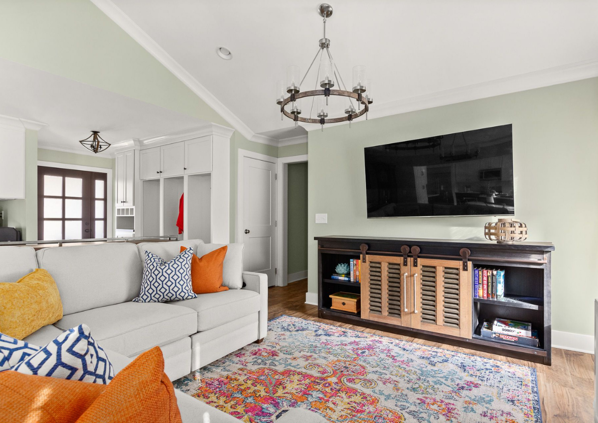 superior-construction-and-design-mt-juliet-tn-color-in-the-home-living-area-mounted-tv-colorful-area-rug-orange-and-blue-pillows