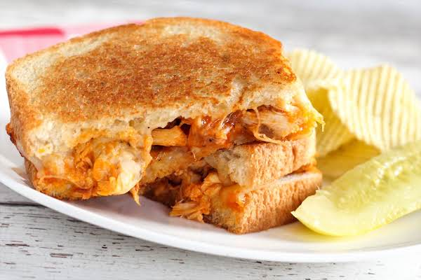 Buffalo Chicken Grilled Onions And Cheese Sandwich On A Plate With Chips.