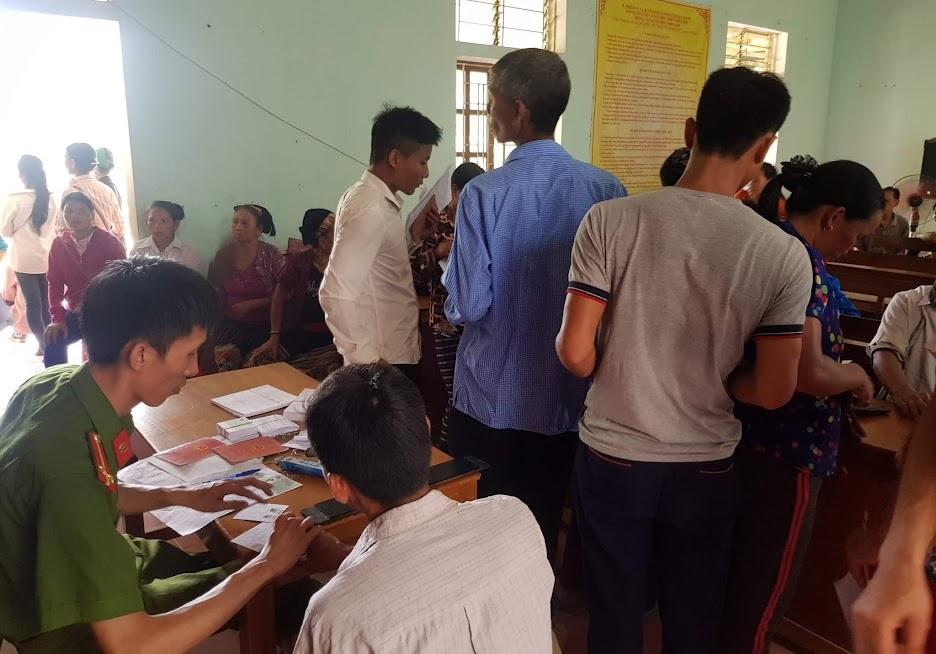 Cán bộ Công an huyện Tương Dương làm thủ tục cấp phát CMND cho bà con tại xã Hữu Khuông.