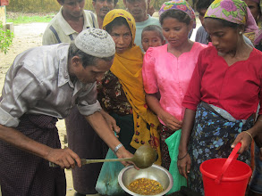 Photo: At a food distribution site near Sittwe, these mothers receive rations of hot meals consisting of rice and mung beans.