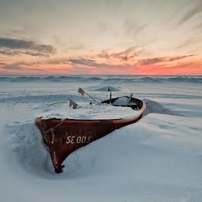 Abandoned by Eriks Zilbalodis - Landscapes Sunsets & Sunrises ( orange, red, winter, sunset, snow, white, boat )
