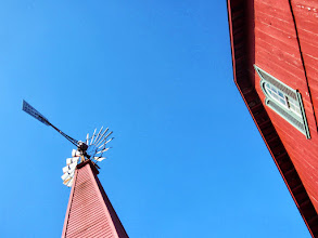 Photo: Red windmill and barn under a blue sky at Carriage Hill Metropark in Dayton, Ohio.