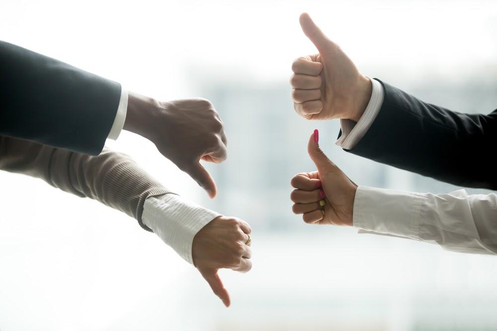 Várias mãos fazendo símbolos de aprovações e desaprovações.