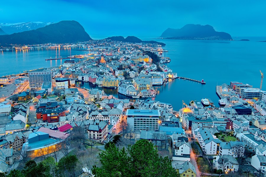 City of Alesund in Norway by Péter Mocsonoky - City,  Street & Park  Vistas ( port, illuminated, reflection, europe, street, cityscape, travel, architecture, house, landscape, coastline, panorama, coast, fjord, island, mountains, sky, alesund, nature, scandinavian, houses, scandinavia, art, beautiful, twilight, sea, tourism, scenic, urban, landmark, european, norwegian, blue, outdoors, background, summer, night, town, view, panoramic,  )
