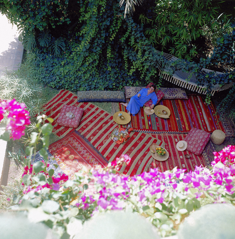 Designer Yves Saint Laurent reclining in his leafy Moroccan garden, strewn with rugs and pillows, wearing a blue caftan.