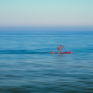 Stand up paddle board man paddleboarding standing on paddleboard on blue water.jpg