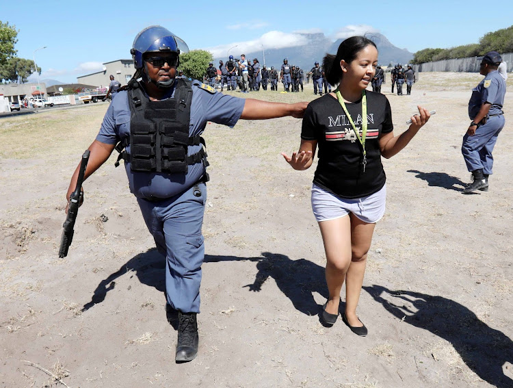 A female student at the Western Cape College of Nursing in Athlone is arrested by a member of the public order police.
