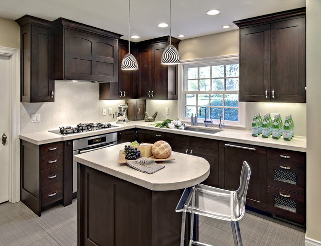 dark espresso shaker cabinets bring contrast to this small l-shaped kitchen. under cabinet lighting illuminates the space, while a simple white backsplash and grey floors brighten up the color palette