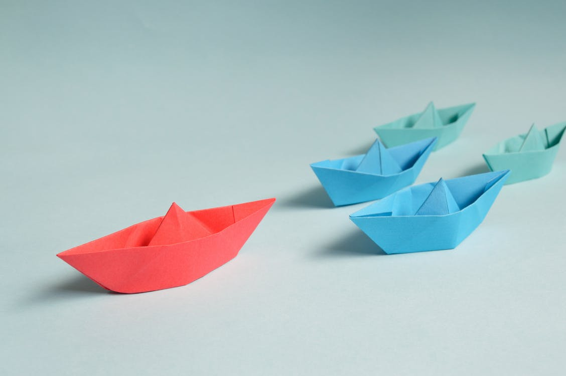 Paper Boats on Solid Surface showing a leader in red boat among blue boats a fleet manager as an example