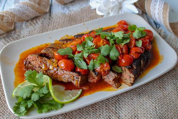 Skirt Steak With Tomatoes On A Platter.