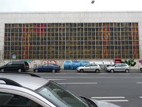 Photo: Das Glasfenster von außen, Totale. Insgesamt 296 (37 × 8) Scheiben (à 93,5 cm × meist 78 cm = 0,73 m² ) gleich 217,3  m² Glas. Rahmen aus Rand und 14 dicken und (36-14=) 22 dünnen Streben (= 14 × 7 cm + 22 × 4 cm = 186 cm. Gesamtbreite geschätzt (37 × 78 cm + 186 cm =) 30,72 m, Höhe (8 × 93,5 cm + 9 × 4 cm =) 7,84 m. Gesamtfläche ca. 240 m². Frühere Angaben 8,01 × 29,5 m = 236 m².