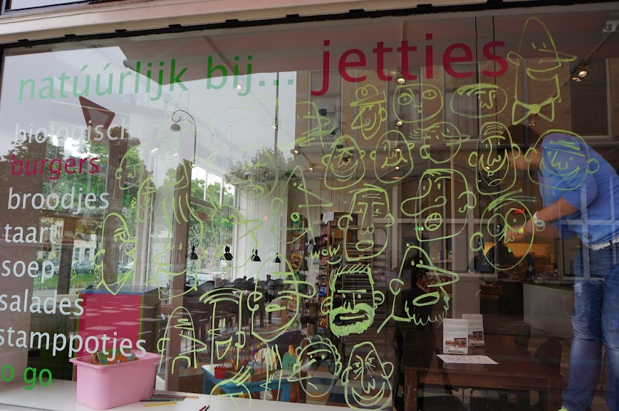 An artist decorates the window of a cafe in Haarlem, Holland (2014)