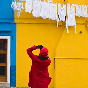 Girl in red shooting laundry with blue and yellow building. by Gale Perry - People Street & Candids ( primary colors, girl, dressed in red, burano, blue and yellow building, white laundry,  )