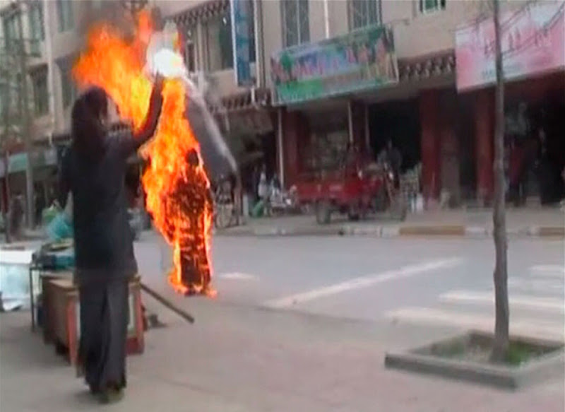 Photo: A woman throws a white scarf over Tibetan Buddhist nun Palden Choetso as she burns on the street in Daofu, or Tawu in Tibetan, in this still image taken from video shot on November 3, 2011 and released to Reuters on November 22. The 35-year-old Tibetan Buddhist nun burned herself to death on the public street, the latest in a string of self-immolations to protest against Chinese religious controls over Tibet. (Reuters/Students For A Free Tibet via Reuters TV) #   A woman throws a white scarf over Tibetan Buddhist nun Palden Choetso as she burns on the street in Daofu, or Tawu in Tibetan,