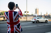 A vote LEAVE supporter takes a photo of Parliament from outside Vote Leave HQ, Westminster Tower on June 24, 2016 in London, England. The United Kingdom has gone to the polls to decide whether or not the country wishes to remain within the European Union. After a hard fought campaign from both REMAIN and LEAVE the vote is awaiting a final declaration and the United Kingdom is projected to have voted to LEAVE the European Union. Picture Credit: Getty Images/Chris J Ratcliffe
