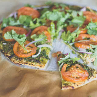 Chickpea Crusted Vegan Pizza with Baby Kale Leaves.