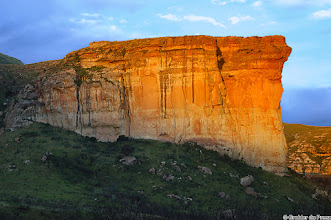 "Photo: The Brandwag (sentinel) in the Golden Gate Highlands National Park (South Africa). The park's most notable features are its golden, ochre, and orange-hued deeply eroded sandstone cliffs and outcrops. ""Golden"" origins from the golden colour when the last rays of the setting sun fall on the cliffs and ""Gate"" refers to the Brandwag (Sentinel) standing guard at the entrance to the park."