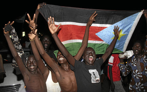 South Sudanese civilians display their national flag as they celebrate the signing of a ceasefire and power sharing agreement between President Salva Kiir and rebel leader Riek Machar, in Khartoum; along the streets of Juba, South Sudan, on August 5 2018. Picture: REUTERS/SAMIR BOL