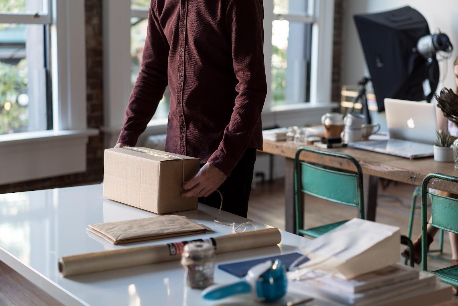 Man in office wraps a cardboard box