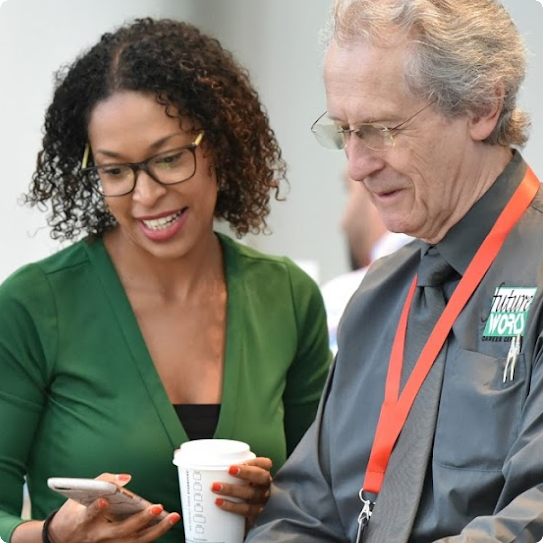 A woman shows a man something on her phone. The woman is smiling.
