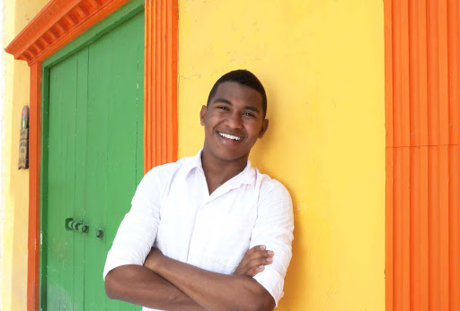Young-Cuban-Man-Agianst-Colorful-Wall_01.jpg - Each Fathom cruise to Cuba includes opportunities to meet local artists.