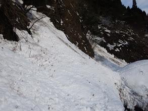 雪崩れた雪の斜面を進む