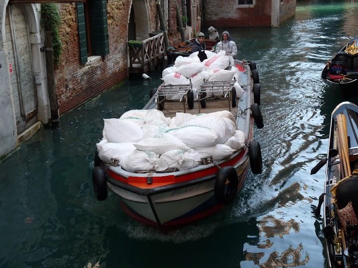 Frachtboot im Kanal, daneben zerbröselndes Mauerwerk.