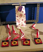 Photo: Medale za 4 pierwsze miejsca, w tle ręczniczek na otarcie łez dla ostatniego miejsca