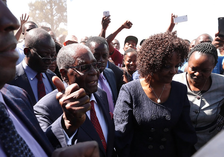 Former Zimbabwean president Robert Mugabe, accompanied by his wife Grace, arrives to vote in the general elections in Harare, Zimbabwe, July 30, 2018.