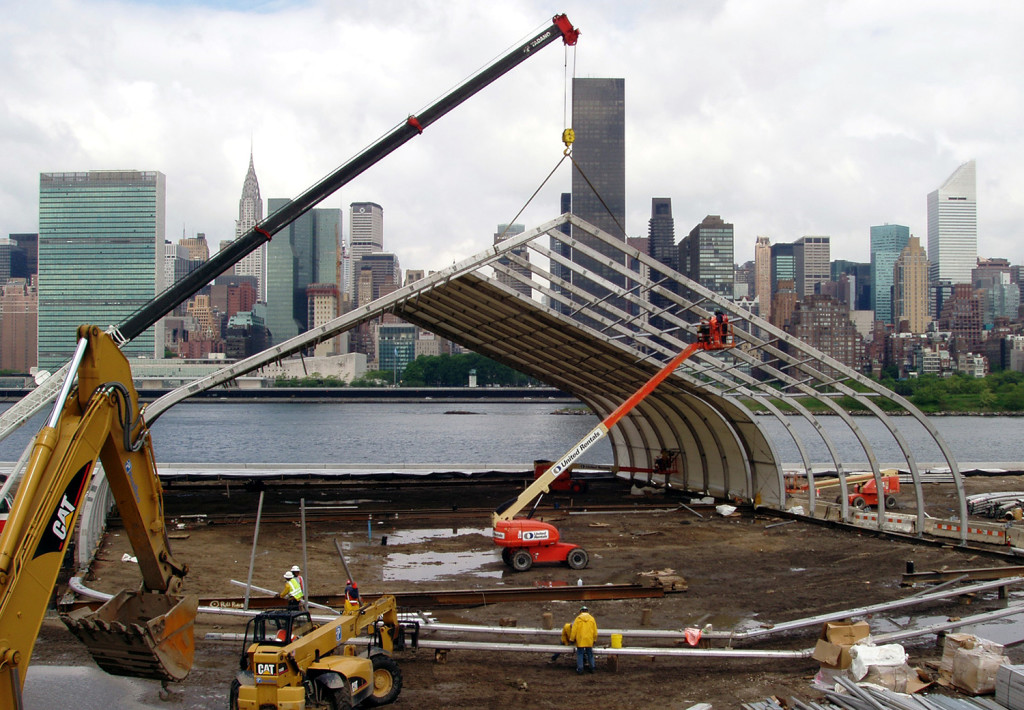 Construction of a tension fabric structure with aluminum frame installed over a worksite on the New York harbor