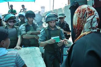 Photo: An Israeli soldier inspects a Palestinian woman's ID card at Qalandiya checkpoint.