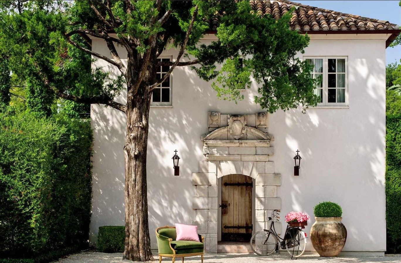 Breathtaking French Country home exterior with stucco exterior, tile roof, limestone, and rustic antique door. #frenchcountry #homeideas #homedesign #curbappeal #mediterranean #stucco #frenchfarmhouse