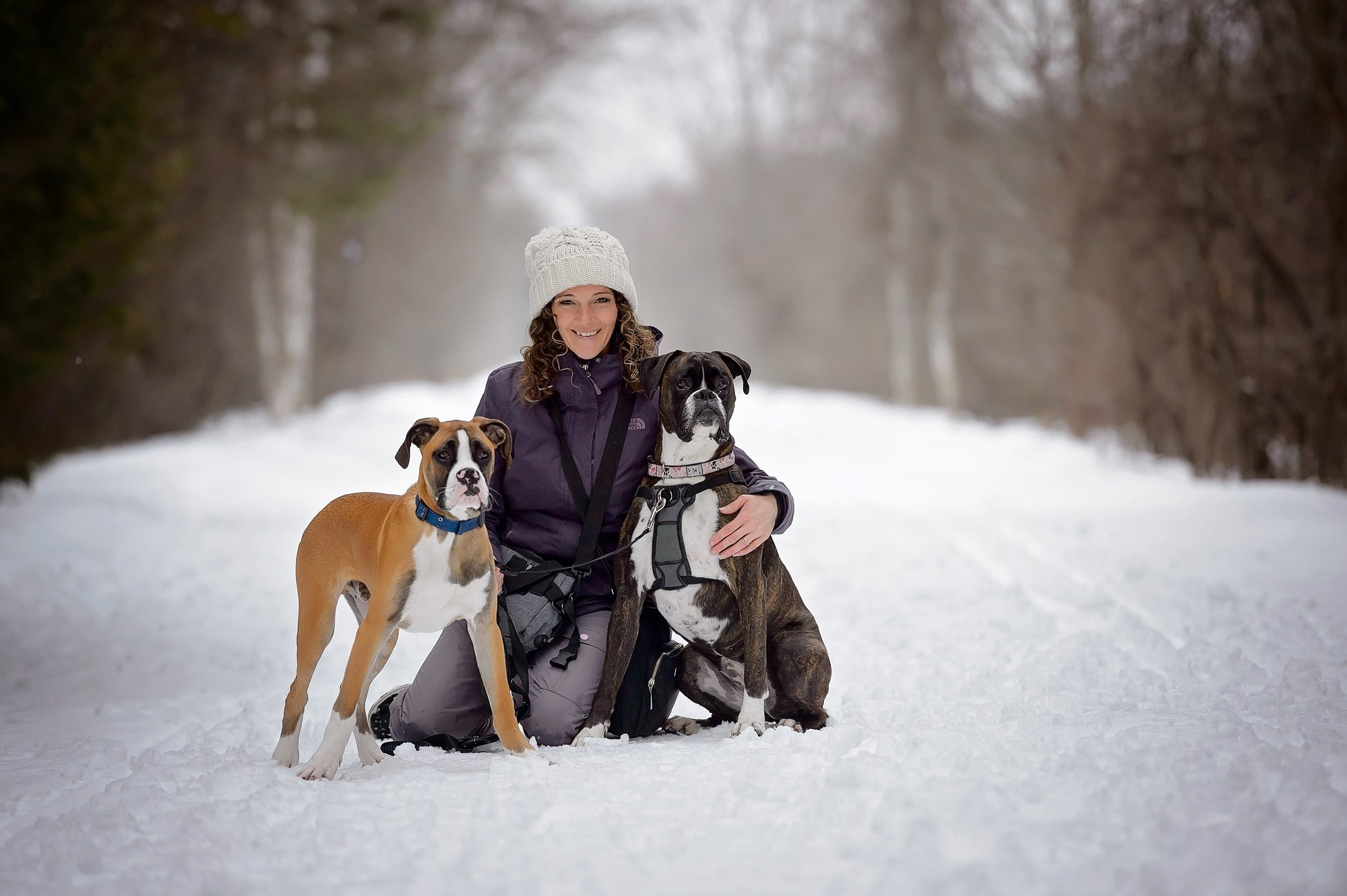 A woman (Nancy) smiles for the camera while hugging two dogs, during a winter walk.