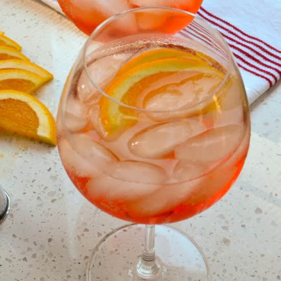 A Quick And Easy Aperol Spritz Made With Three Ingredients Splashed Over Ice And Garnished With Orange Slices.  This Beautiful Cocktail Is Sure To Become One Of Your Summer Favorites.