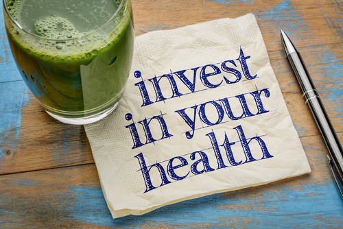 a note with with text reading invest in our health with a filled green mug sitting next to it