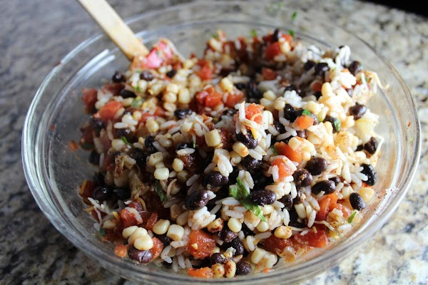 In a bowl, mix together cooked rice, beans, corn, onion, tomatoes, cilantro, cumin, chili...
