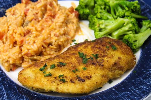 Parmesan Crusted Chicken With Creamy Risotto On A Plate.